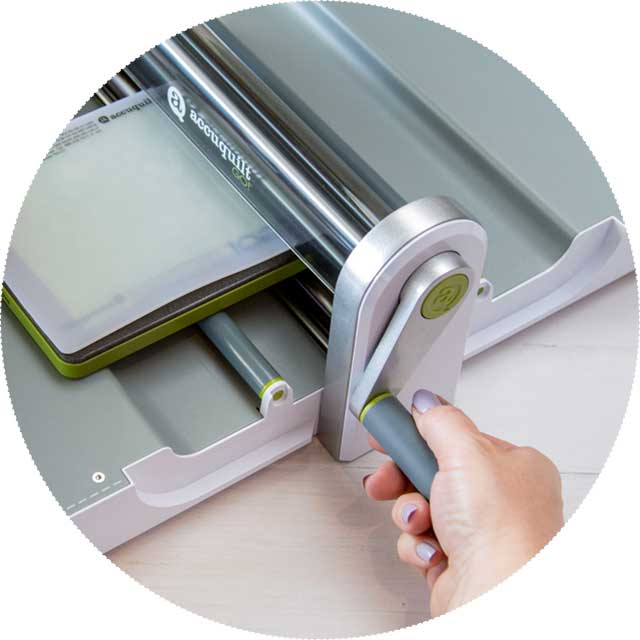 Turn the handle to roll the cutting die through the fabric cutter